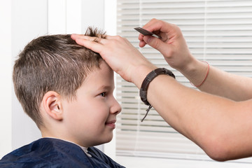 hairdresser stylist makes a hairstyle for a boy with a comb