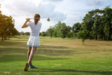 Beautiful girl playing golf on beautiful sunny green golf course. Hitting golf ball down the fairway from the tee with driver. Golfer hitting ball with club on beatuiful golf course