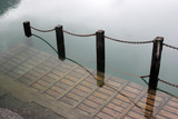 Waterlogged wooden platform with metal chain railing on a river bank - 220375773