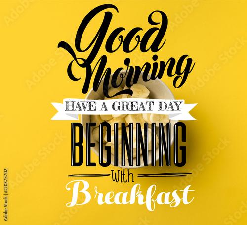 """Widok z góry miska z wyciętymi bananami na żółtym tle z inspiracją """"Dzień dobry, miłego dnia, począwszy od śniadania"""""""