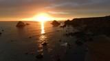 Panning across a spectacular sunset over a rocky ocean coastline. - 220378996