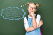 pensive schoolchild in glasses looking up near blackboard with words on different languages in speech bubble
