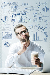 thoughtful developer sitting at workplace with SEO ideas and icons