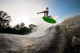 Young attractive man jumping on the green wakeboard on the lake - 220400377