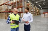 logistic business, shipment and people concept - warehouse worker and businessman with clipboard and tablet pc computer