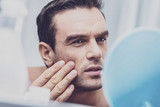 Skin checking. Close up of handsome focused man critically examining his face skin in the mirror and touching his cheeks with fingers - 220402169