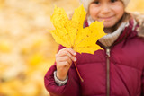 childhood, season and people concept - close up of little girl with maple leaf in autumn - 220402581
