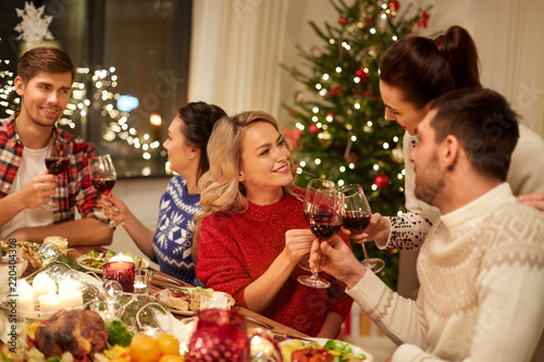 holidays and celebration concept - happy friends having christmas dinner at home, drinking red wine and clinking glasses - 220404308