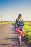 a girl with an American flag on her hips walking along the road. symbol of freedom, choice - 220436943