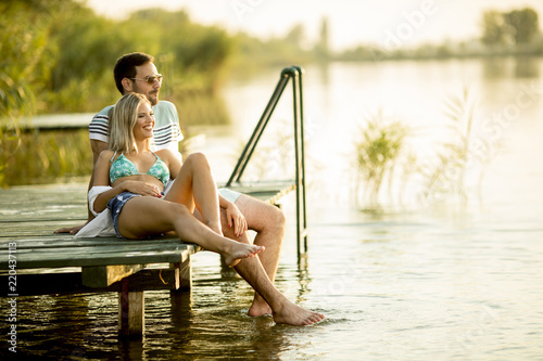 Leinwanddruck Bild Romantic couple sitting on the wooden pier on the lake