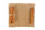 cinnamon sticks on burlap on white background - 220440981