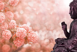 Side view of Buddha statue, peach and white flowers in background with bokeh effect and ray of light. - 220446179