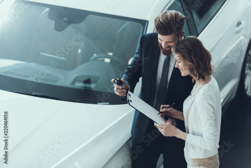 Car Salesman Consultant Showing Contract to Woman - 220464156