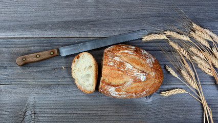 whole loaf of bread with cutting knife and stalks on rustic wooden boards