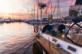 Sailboat with wooden deck standing in marine at beautiful sunset - 220481527