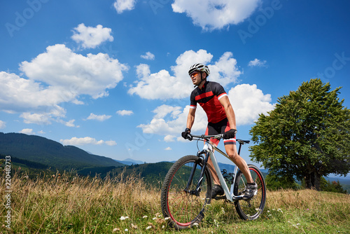 Professional male biker in sportswear and helmet cycling bike on a trail. Athlete rider enjoying beautiful view of Carpathian mountains on sunny summer day. Active lifestyle and outdoor sport concept