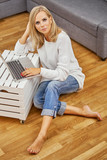 beautiful blonde girl wearing jeans sitting on the floor and working on the computer - 220482952