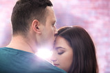 Portrait of young loving couple on blurred background - 220496162