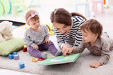 Young nanny with cute little children, indoors - 220496321