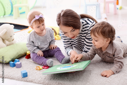 Young nanny with cute little children, indoors