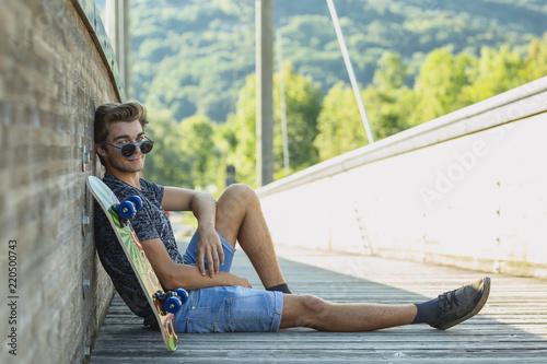 Fototapeta Boy sitting near skateboard at bridge