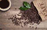 Kaffeesack mit Kaffeebohnen und Kaffeetasse auf Holzbrett - 220506774