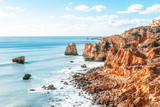 Panorama of Praia da Marinha on the south coast of Portugal in the Algarve on a sunny day. The cliffs, beach and Atlantic ocean are in view with tourists on the beach
