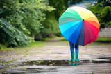 Child walking in wellies in puddle on rainy weather. Boy holding colourful umbrella under rain in summer - 220529950