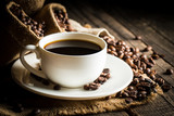 Coffee cup and beans on a rustic background. Coffee Espresso and a piece of cake with a curl. Cup of Coffee and coffee beans on table. - 220531327