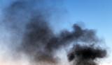 black smoke pillar against the blue sky background. - 220533123