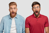 Friendship and emotions concept. Stunned emotive two men keep jaw dropped, wonder seasonal discounts and prices, stand next to each other, have trendy haircuts and beards, isolated on white. - 220535371