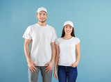 Young man and woman in stylish white t-shirts on color background. Mockup for design - 220537101