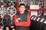 Young mechanic with car tires in store - 220537107