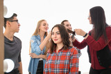 Professional hairdresser and trainees working with client in salon. Apprenticeship concept - 220537139