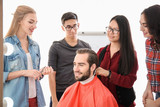 Professional hairdresser and trainees working with client in salon. Apprenticeship concept - 220537141