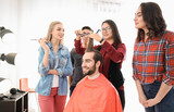 Professional hairdresser and trainees working with client in salon. Apprenticeship concept - 220537146