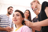 Professional hairdresser and trainees working with client in salon. Apprenticeship concept - 220537159