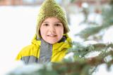 Cute boy near fir tree in park on winter vacation - 220537166