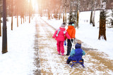 Children walking in snowy park on winter vacation - 220537167