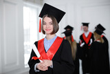 Happy student in bachelor robe with diploma indoors. Graduation day - 220537169