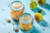 Homemade and healthy pickled pears on blue table - 220553103