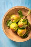 Sweet pears on the wooden bowl and blue table - 220553148