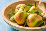 Juicy pears on the wooden bowl and blue table - 220553165
