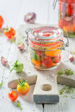 Natural and healthy canned red tomatoes in the jar - 220553335
