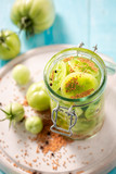 Homemade and tasty pickled green tomatoes in the jar - 220553507