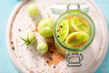 Natural and healthy pickled green tomatoes on blue table - 220553509