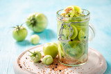 Natural and healthy pickled green tomatoes in the jar - 220553522