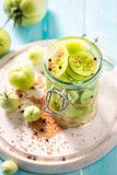 Preparation for fresh pickled green tomatoes on blue table - 220553533