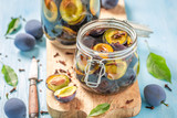 Natural pickled purple plums in the jar - 220553545