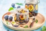 Tasty pickled purple plums in the jar - 220553581